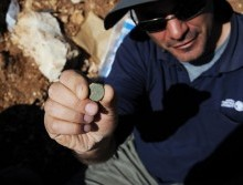 Pablo Betzer, IAA District Archaeologist for Judah, with a coin from the Year Four of the Great Revolt. By Vladimir Niihin, courtesy of the Israel Antiquities Authority.