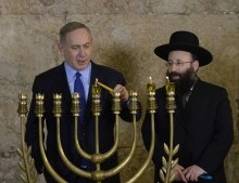 Israeli PM Netanyahu lights the Hanukkiah candelabra at the Western Wall. Photo Courtesy of Amos Ben-Gershom (GPO)